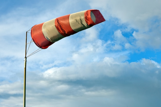 Meteorology wind bag for marine navigation. red and white windsock blows against a blue sky