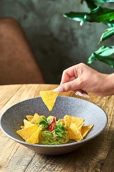 Мексиканский авокадо гуакамоле с начо, острым перцем и базиликом в серой тарелке. руки окунают начо в гуакамоле