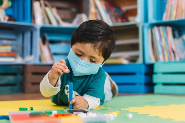 Mexican baby in school with face mask playing with colored pieces on a mat