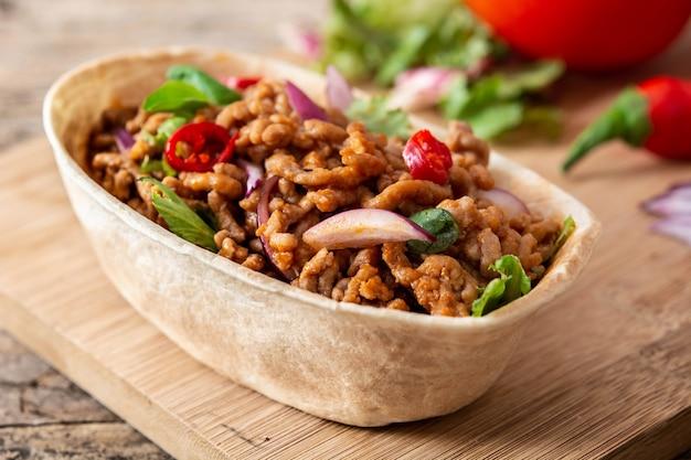 牛肉、唐辛子、トマト、タマネギ、スパイスを木製のテーブルに乗せたメキシコのバルキータタコス