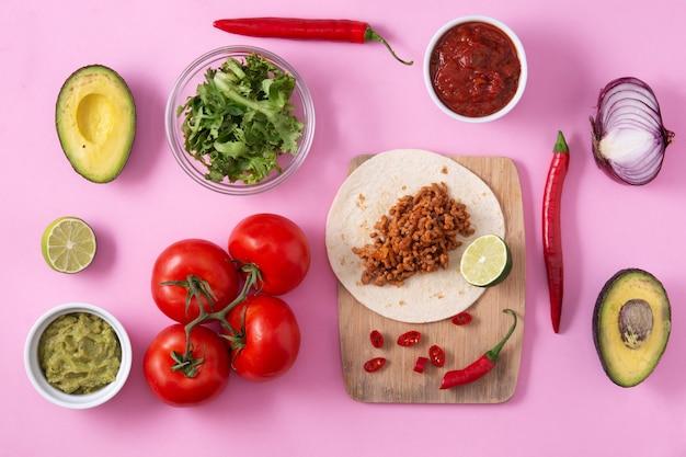 Мексиканский тако баркита с говядиной, перцем чили, помидорами, луком и специями на розовом фоне