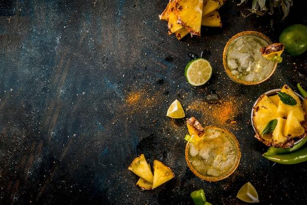 パイナップルとハラペーニョとライムの暗い青色の背景を持つメキシコ飲料スパイシーなマルガリータカクテル