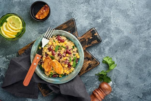 어두운 회색 콘크리트 배경에 오래 된 빈티지 점토 그릇에 캐러멜 레몬 멕시코 검은 콩 옥수수 노아 샐러드. 전통적인 멕시코 요리 요리. 상위 뷰, 모의.