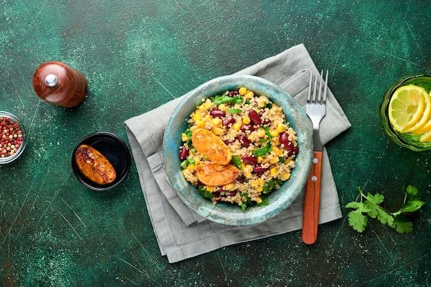 어두운 녹색 콘크리트 표면에 오래 된 빈티지 점토 그릇에 캐러멜 레몬과 멕시코 검은 콩 옥수수 노아 샐러드. 전통적인 멕시코 요리 요리. 평면도,