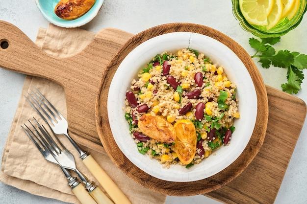 밝은 회색 콘크리트 배경에 오래 된 빈티지 점토 그릇에 캐러멜 레몬과 멕시코 검은 콩 옥수수 노아 샐러드. 전통적인 멕시코 요리 요리. 상위 뷰, 모의.