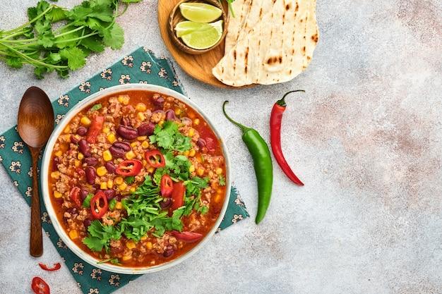 다진 고기, 토마토, 실란트로, 아보카도, 야채를 곁들인 멕시코 검은콩 수프는 밝은 회색 슬레이트, 돌 또는 콘크리트 배경에 스튜입니다. 전통적인 멕시코 요리입니다. 복사 공간이 있는 상위 뷰입니다.