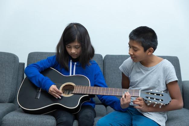 ギターを弾くことを学ぶメキシコの少年と少女