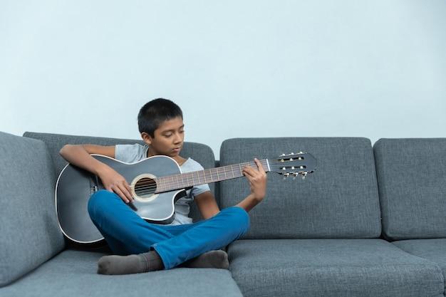 自宅でギターを弾くメキシコの少年、ホームスクーリング
