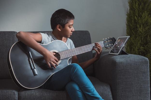 코로나 바이러스 봉쇄, 홈 스쿨링으로 인해 집에서 기타 레슨을받는 멕시코 소년