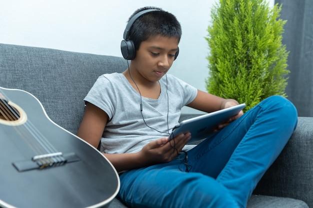 コロナウイルスの封鎖、ホームスクーリングのために自宅でギターのレッスンを受けているメキシコの少年