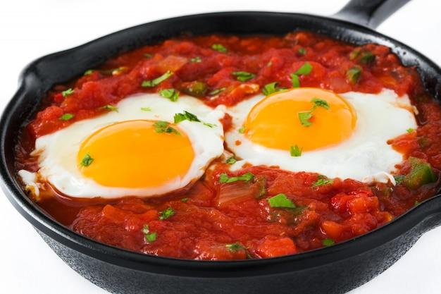白い背景に分離された鉄のフライパンでメキシコの朝食huevos rancherosをクローズアップ
