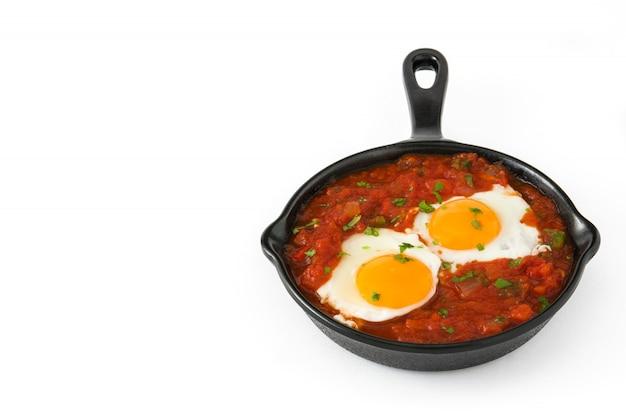 白い背景のコピースペースに分離された鉄のフライパンでメキシコの朝食huevos rancheros
