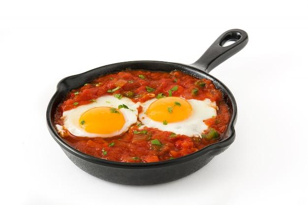 白い背景に分離された鉄のフライパンでメキシコの朝食huevos rancheros