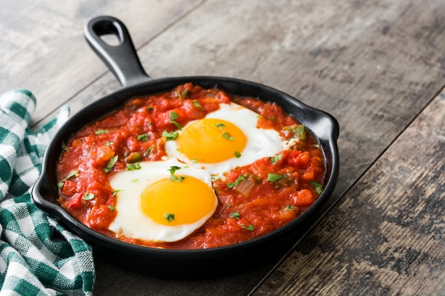 木製のテーブルに鉄のフライパンでメキシコの朝食huevos rancheros