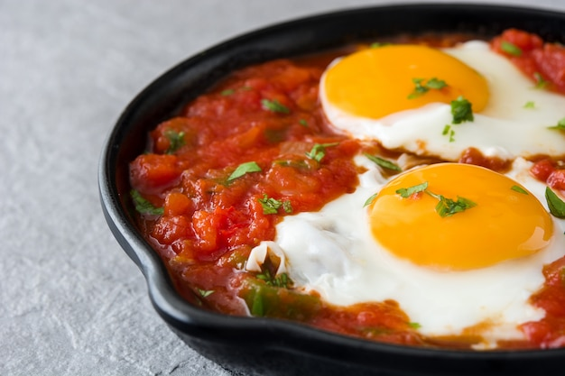 Mexican breakfast huevos rancheros in iron frying pan on gray stone close up