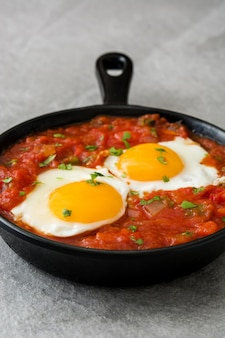 Mexican breakfast huevos rancheros in iron frying pan on gray stone