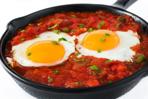 Mexican breakfast huevos rancheros in iron frying pan isolated on white background close up