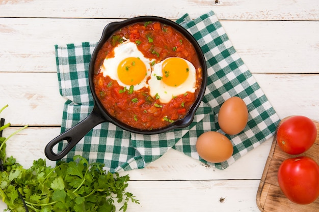 Mexican breakfast, huevos rancheros in iron frying pan on white wood table top view