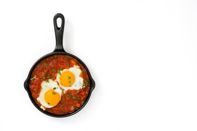 Mexican breakfast huevos rancheros in iron frying pan on white