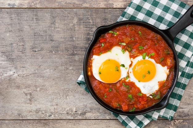 Mexican breakfast, huevos rancheros in iron frying pan on wood table top view