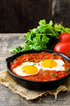 Mexican breakfast: huevos rancheros in iron frying pan on wooden table