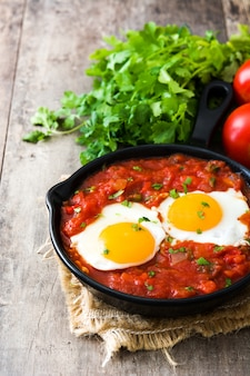 Mexican breakfast huevos rancheros in iron frying pan on wooden table