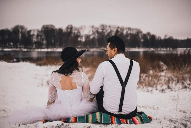 Mexican bride and groom in wedding clothes and suspenders sit on the snow in winter