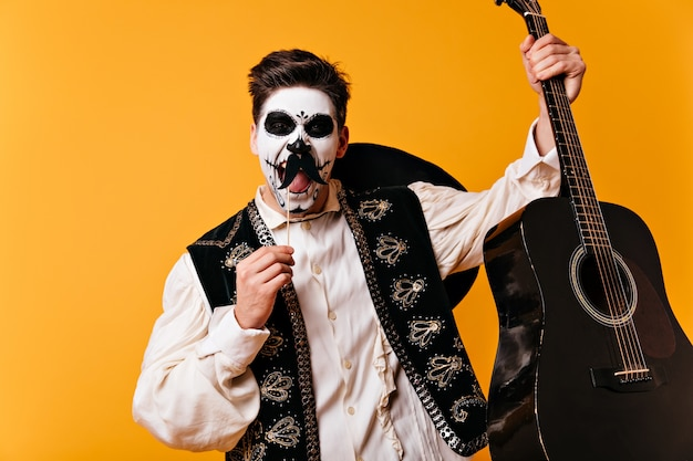 頭蓋骨の形の顔の芸術を持つメキシコの茶色の目の男は、オレンジ色の壁に彼の手で偽の口ひげとギターでポーズをとって、感情的に叫びます。