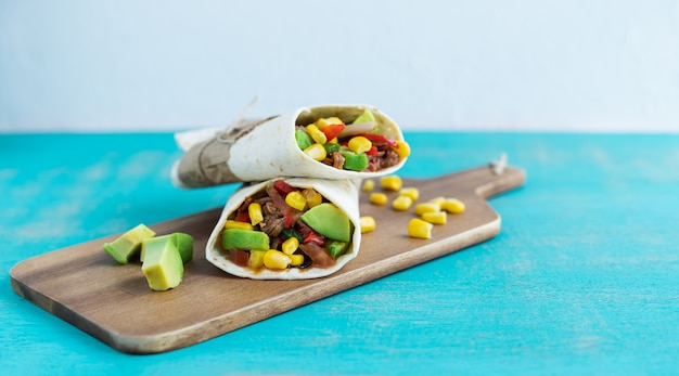 Mexican burritos on a kitchen table on a blue background. mexican cuisine concept. copy space.