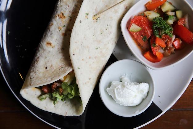 トマトサラダとプレート上のメキシコのブリトー
