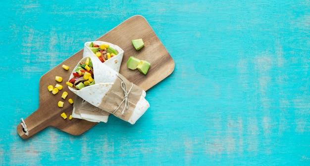 青色の背景に木の板にメキシコのブリトー。典型的なメキシコ料理のコンセプト。コピースペース。