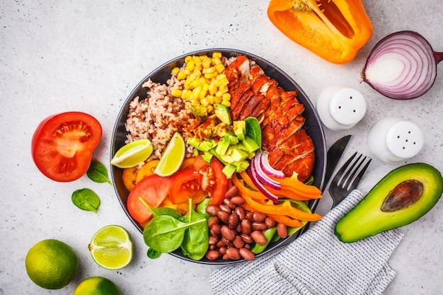 Мексиканская куриная чаша буррито с рисом, фасолью, помидорами, авокадо, кукурузой и шпинатом, на белом фоне. концепция еды мексиканской кухни.
