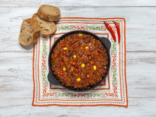 Мексиканский перец чили жулик чили карне в сковороде на белый деревянный стол.
