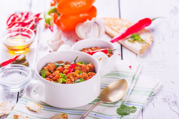 Mexican chili con carne with ingredients on white wooden table.