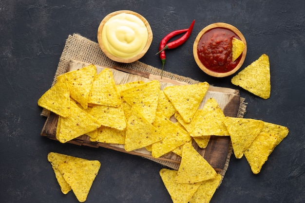 Mexican corn chips nachos with sauces on dark background. top view.