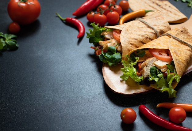Mexican corn tortilla wrap with grilled chicken and fresh vegetables