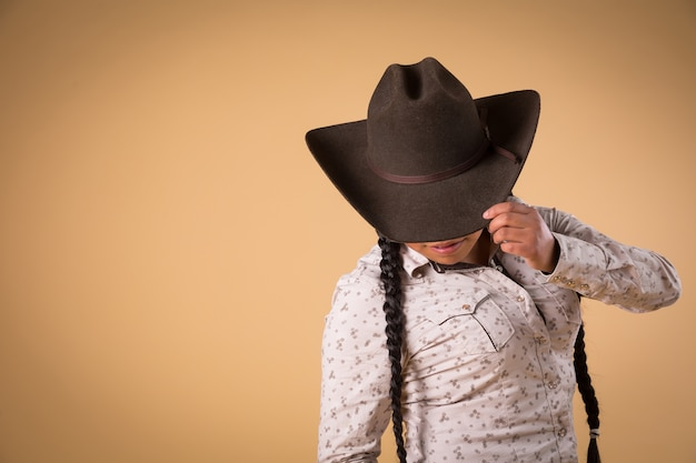 Mexican cowgirl holding hat isolated on brown background
