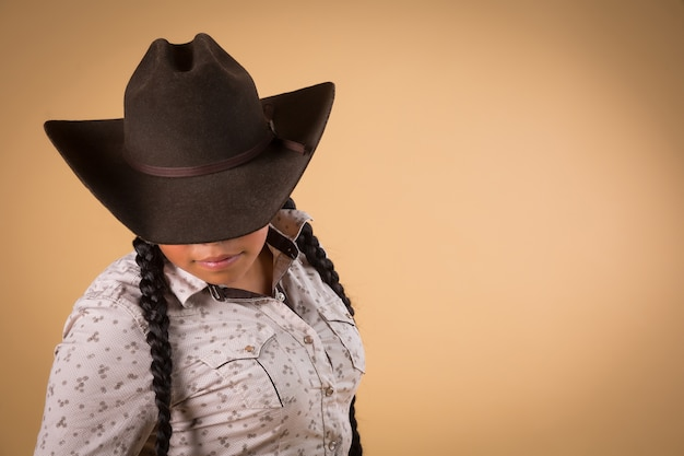 Mexican cowgirl isolated on brown background