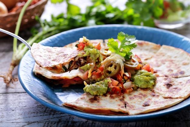 Кесадилья мексиканской кухни подается на синей тарелке с гуакамоле, сальсой и перцем халапеньо
