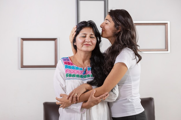 Mexican daughter kissing and hugging her mom on mother's day