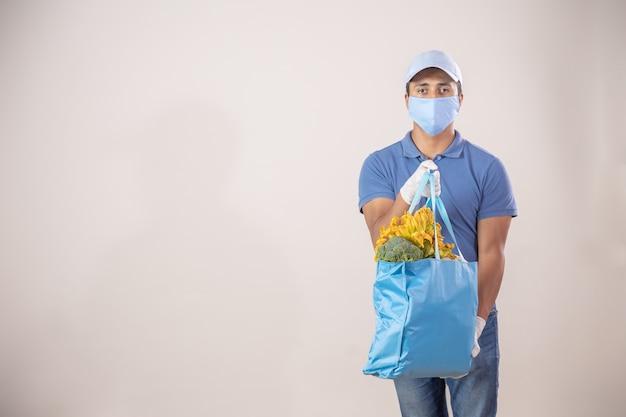 フェイスマスクと手袋を身に着けている果物と野菜の生態学的なバッグを持つメキシコの配達人