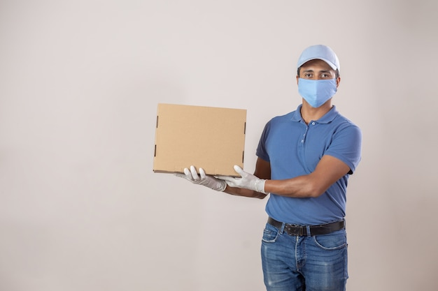Mexican delivery man with mouthpiece and gloves in quarantine showing a cardboard