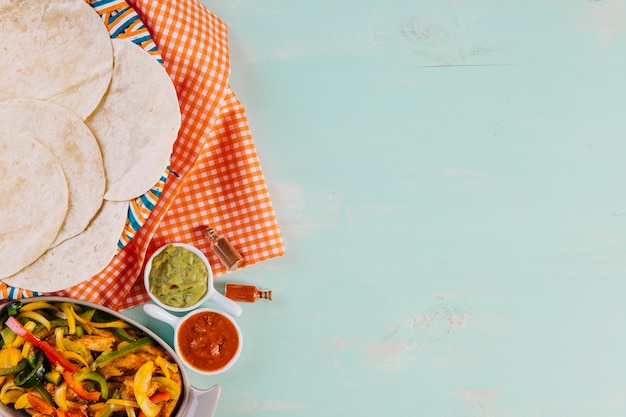Mexican dish near tortillas and tablecloth
