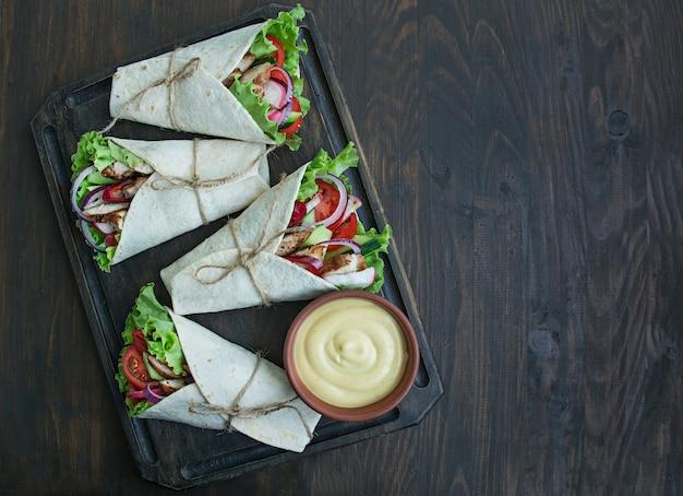 멕시코 요리입니다. 나무 표면에 닭고기와 야채 클로즈업으로 타코.