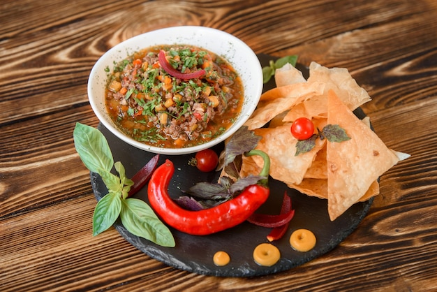 Mexican dish with meat, chili, tomato, corn with nachos in a white plate on a black slate platter, garnished with basil, blue onions and cherry tomatoes. spicy mexican dish on a wooden table.