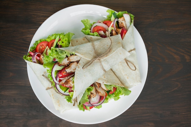 Mexican dish.wrapped burrito with chicken and vegetables close-up on a wooden