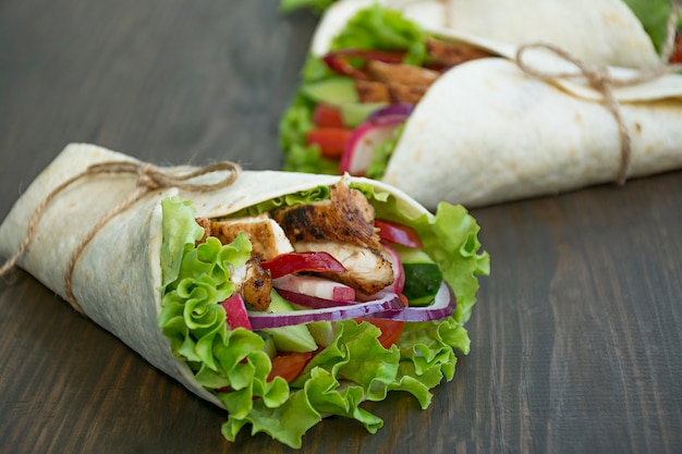 Mexican dish.wrapped burrito with chicken and vegetables close-up