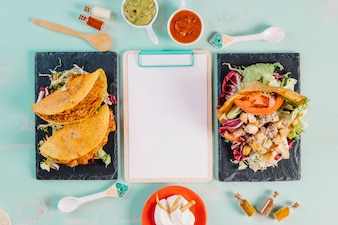 Mexican dishes and spices around clipboard