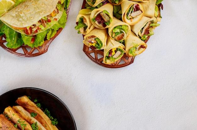 Мексиканские блюда из муки мягких лепешек на столе.