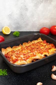 닭고기, 야채, 옥수수, 콩, 치즈와 함께 멕시코 엔칠 라다. 블랙 테이블에 베이킹 트레이에 제공됩니다. 멕시코 음식. 라틴 아메리카 요리. 회색 배경, 가까이, 복사 공간